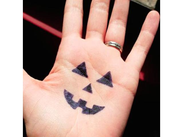 Spooky pumpkin face on hand