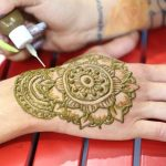 Applying henna to hand
