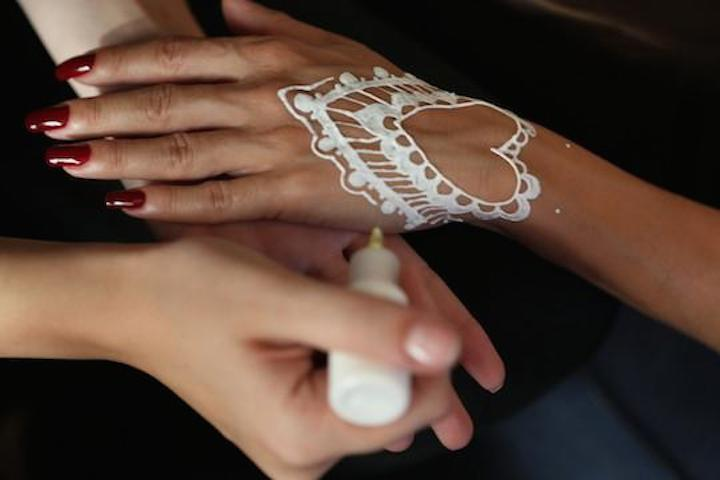 Drawing white henna design on hand