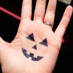 Spooky pumpkin face on hand