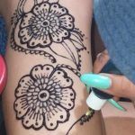 Applying jagua tattoo to arm
